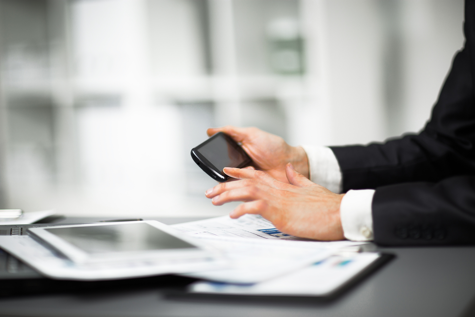 Hand to use a smartphone on the desktop in the office